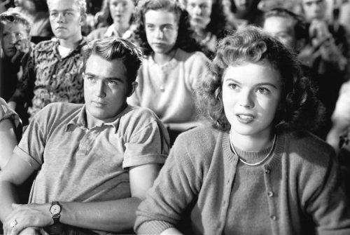 "Medium shot for ""The Bachelor and the Bobby-Soxer"" of Johnny Sands as Jerry White and Shirley Temple as Susan Turner sitting with students in High School auditorium."